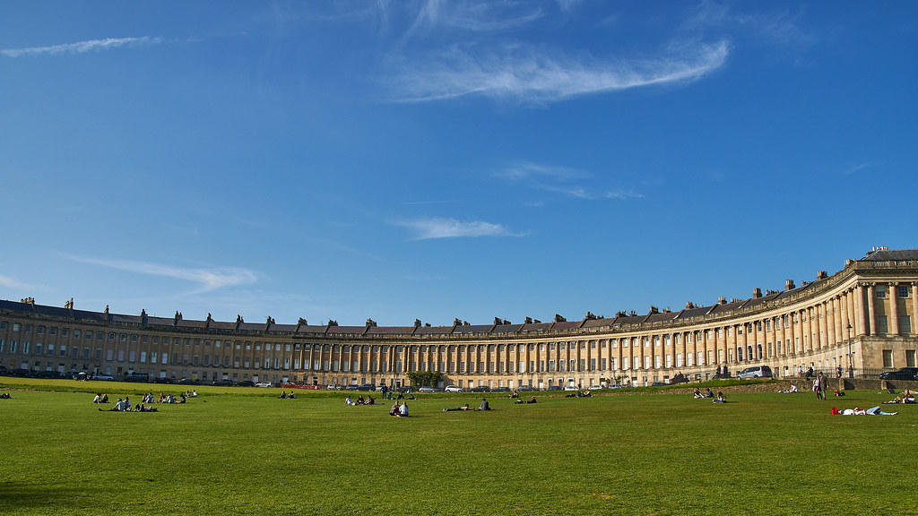 Groups of people sat on the grass in front of the Royal Crescent in Bath