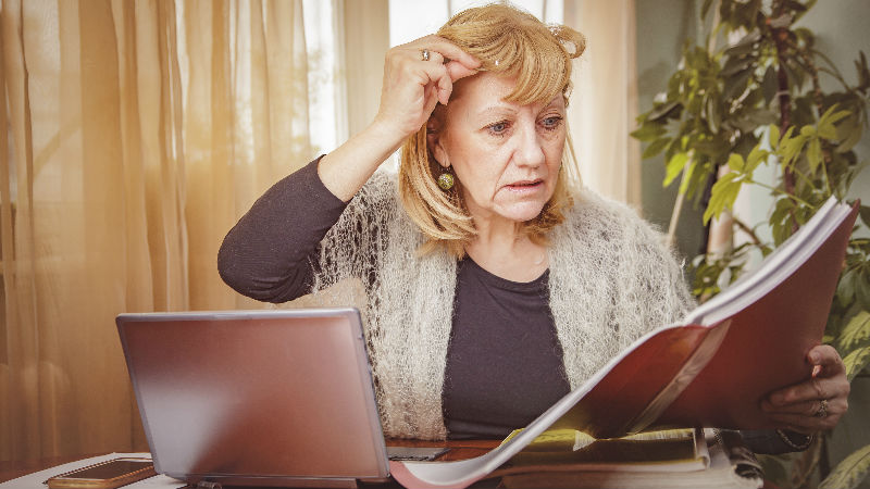 A woman looks at a pensions statement in surprise