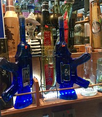 Two tequila bottles shaped like guns in a store window.