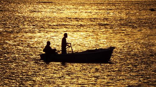 sea fisherman gold sunset water man people
