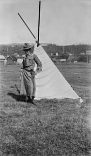 A woman dressed in cowgirl apparel, with her hand on a holstered gun, stands in front of a tent, Prince Rupert, British Columbia / Femme en tenue de cowgirl, la main sur un fusil dans son étui, debout devant une tente à Prince Rupert (Colombie-Britan