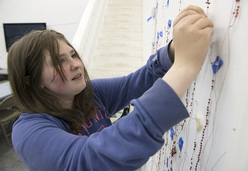Hannah Ellis pins her counting cord to the wall at Yaghanen Youth Center after adding the day's attendance bead.