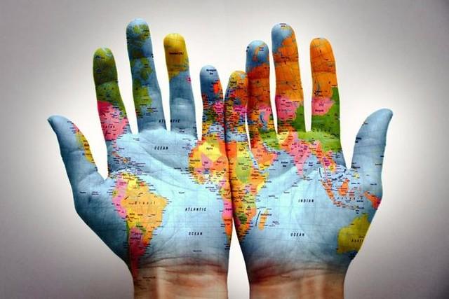 due mani affiancate, con palmi rivolti verso l'alto, con sopra il disegno del mappamondo