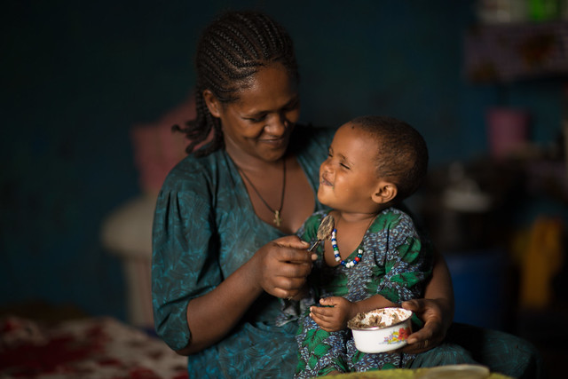 Netsanet, feeding her tow year daughter porridge made of balance nutritional ingredients based on lessons from the wereda health post.