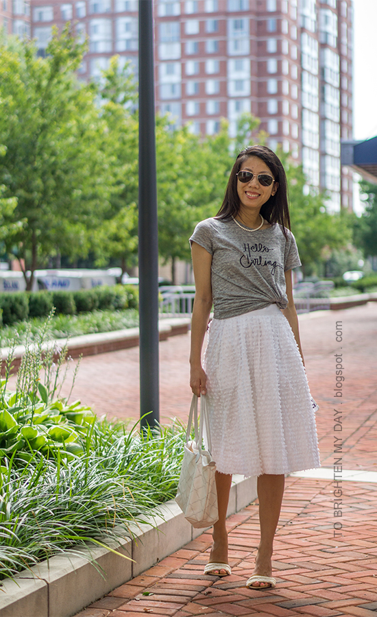 gray graphic tee, pearl necklace, white clip dot midi skirt, white tote bag, white sandals with fringe
