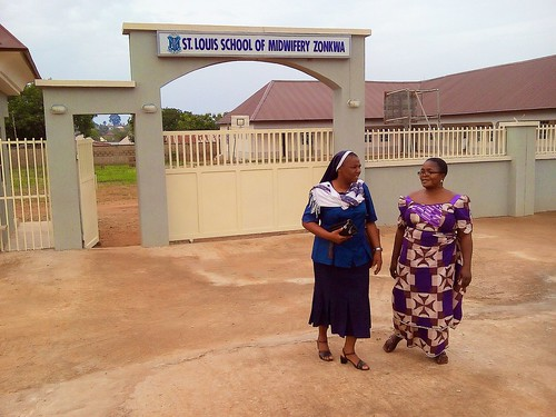 Perpetua Oloba SSL (left) and Mrs Charity Patrick (right) in front of the New auditorium, classrooms and Science building of the St Louis School of Midwifery in Zonkwa