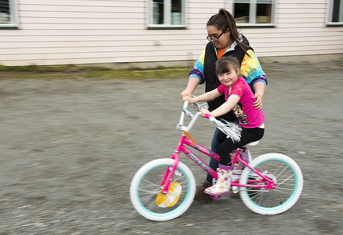 Jessica Segura helps Starla Oskolkoff ride the new bike she received for reading 100 books at the Early Childhood Center.