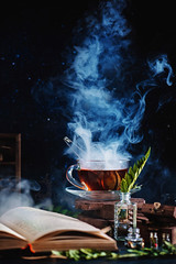 Hot steaming tea with an open book