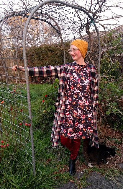 Woman stands in garden archway. She wears handknit yellow hat, checked flannelette long cardigan, black floral dress, burgundy velvet leggings and ankle boots.