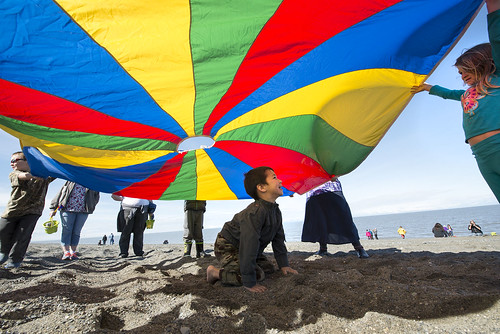 Children play under a colorful tarp during the Early Childhood Center's yearend picnic on the Cook Inlet Beach.