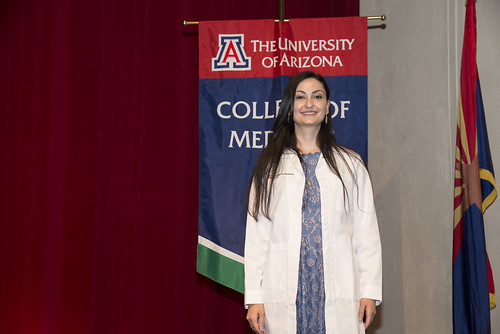 Students in white coats in front of the College of Medicine banner, as well as family shots following the event.
