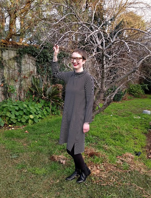 Woman stands in a garden. She wears striped cocoon turtleneck dress with black leggings and ankle boots.