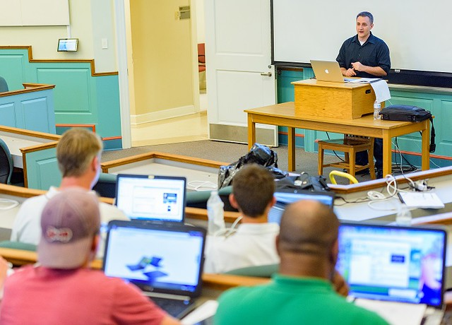 "High school students participating in the 2017 State of Delaware Cyber Camp listen to Iowa State Ph.D. candidate Ben Holland's talk on ""Program Analysis for Cybersecurity."" The camp is part of the U.S. Cyber Challenge, a week-long day camp comprised of cyber security workshops, and labs that ends with a Capture the Flag competition. (Photo courtesy of University of Delaware.)"