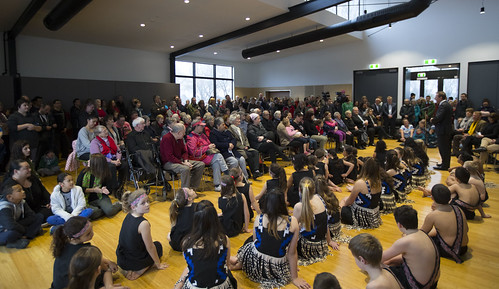 Kapa haka group sit during speeches in the Community Centre