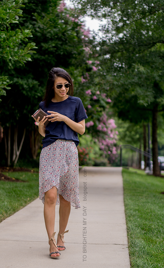 navy silky tee, floral wrap midi skirt, taupe clutch, flower ring, jeweled suede flats with ankle ties