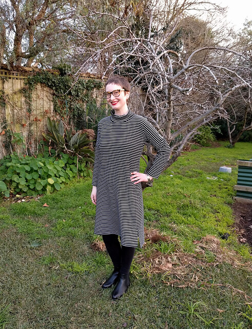 A woman stands in a garden. She wears a black and white striped dress in a cocoon shape with a turtleneck. She is smiling.