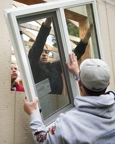 Tatihana DeHoyos, Katrina Conaway and youth tutor Zach Kudla install a window in the cabin built at the K'beq' Cultural Site during the Construction Academy.