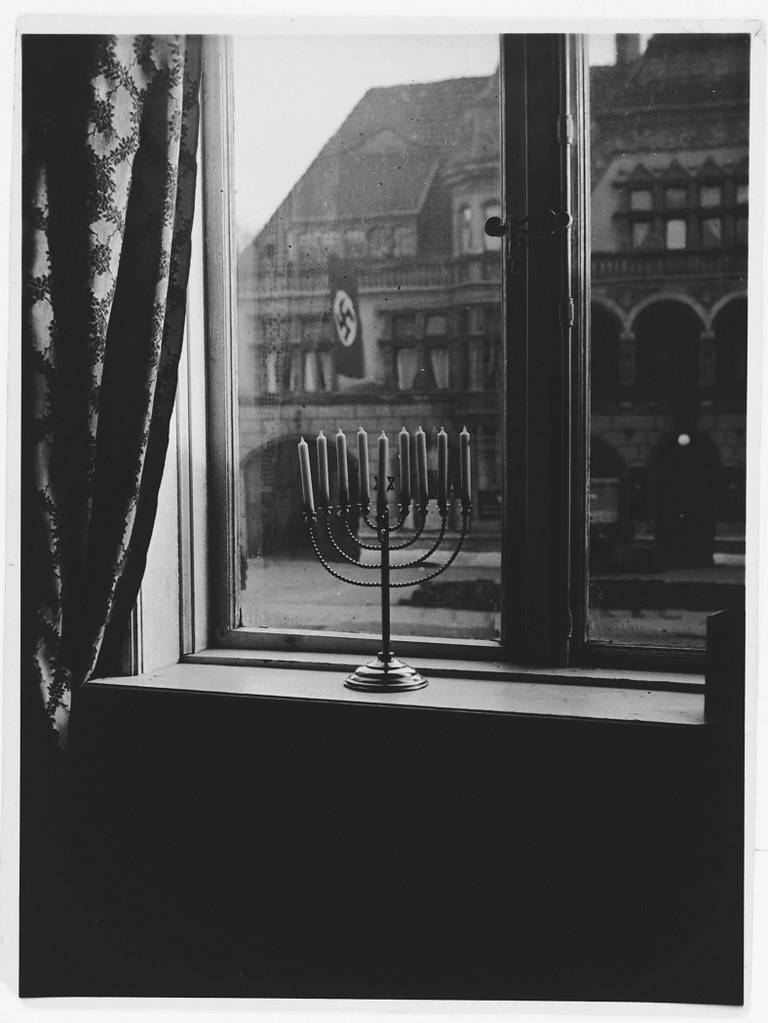 002---A Hanukkah menorah rests on the sill of an apartment window in Kiel---The window looks out on the town hall. The menorah belonged to Rabbi Akiva Posner, the rabbi of Kiel.