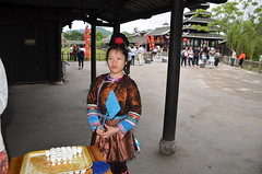 A lass in ethnic clothing welcomes you with rice wine