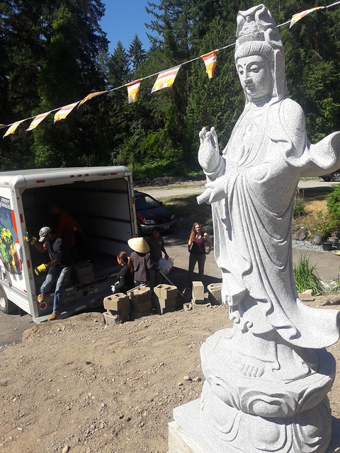 Sangha members unloading brick and preparing to build a garden wall to support marble statute of Lady Quan Yin, the bodhisattva, Vietnamese Buddhist Shrine, Federal Way, Washington, USA