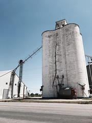"""""""Lone Silo"""" A massive silo, still in use, dominates a tiny village along Route 60 in New Mexico. Industry Architecture Silo Storage Tank Industrial Building  New Mexico Newmexicophotography Route 60 Silos Farming Travel Photography Historical Place at Rou"""