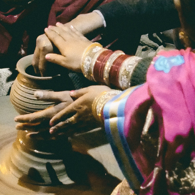 Closeup of newlyweds making pottery at Haveli