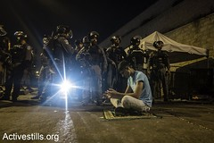 A Palestinian holds his prayer in front of Israeli forces in a street adjacent to #Jerusalem's old town.