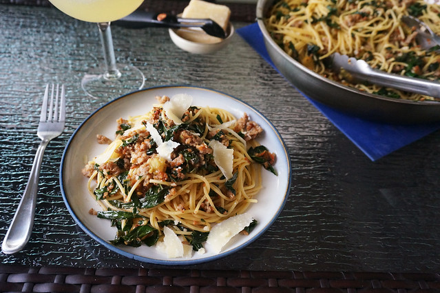 A plate of spaghetti with sausage and kale, swirled nicely upward, sits in front of a wineglass and a big pan of pasta.