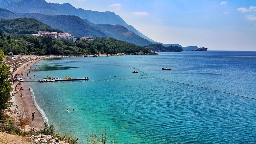 Kamenovo beach in Rafailoviči, Montenegro and view at Sveti Stefan millionaire hotels island in distance