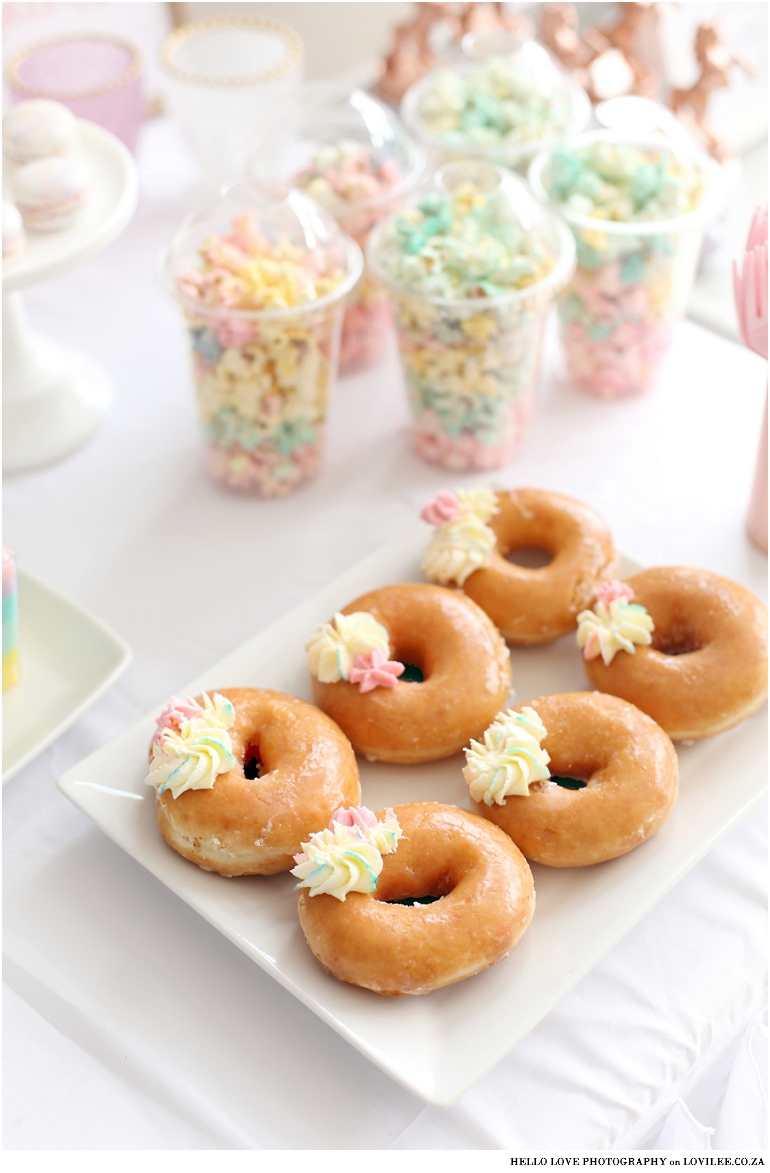 Unicorn party decor - Candy table with rainbow popcorn and doughnuts