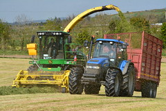 John Deere 7700 SPFH Filling a Redrock Trailer drawn by a New Holland TM120 Tractor