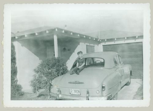 Boy sitting on a car trunk