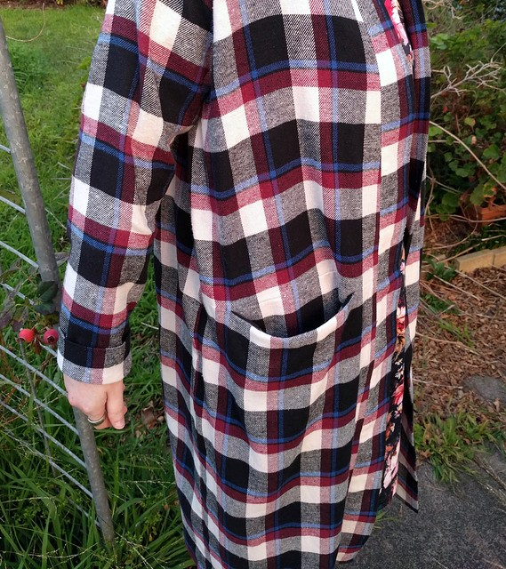 Woman wears checked long flannelette cardigan.