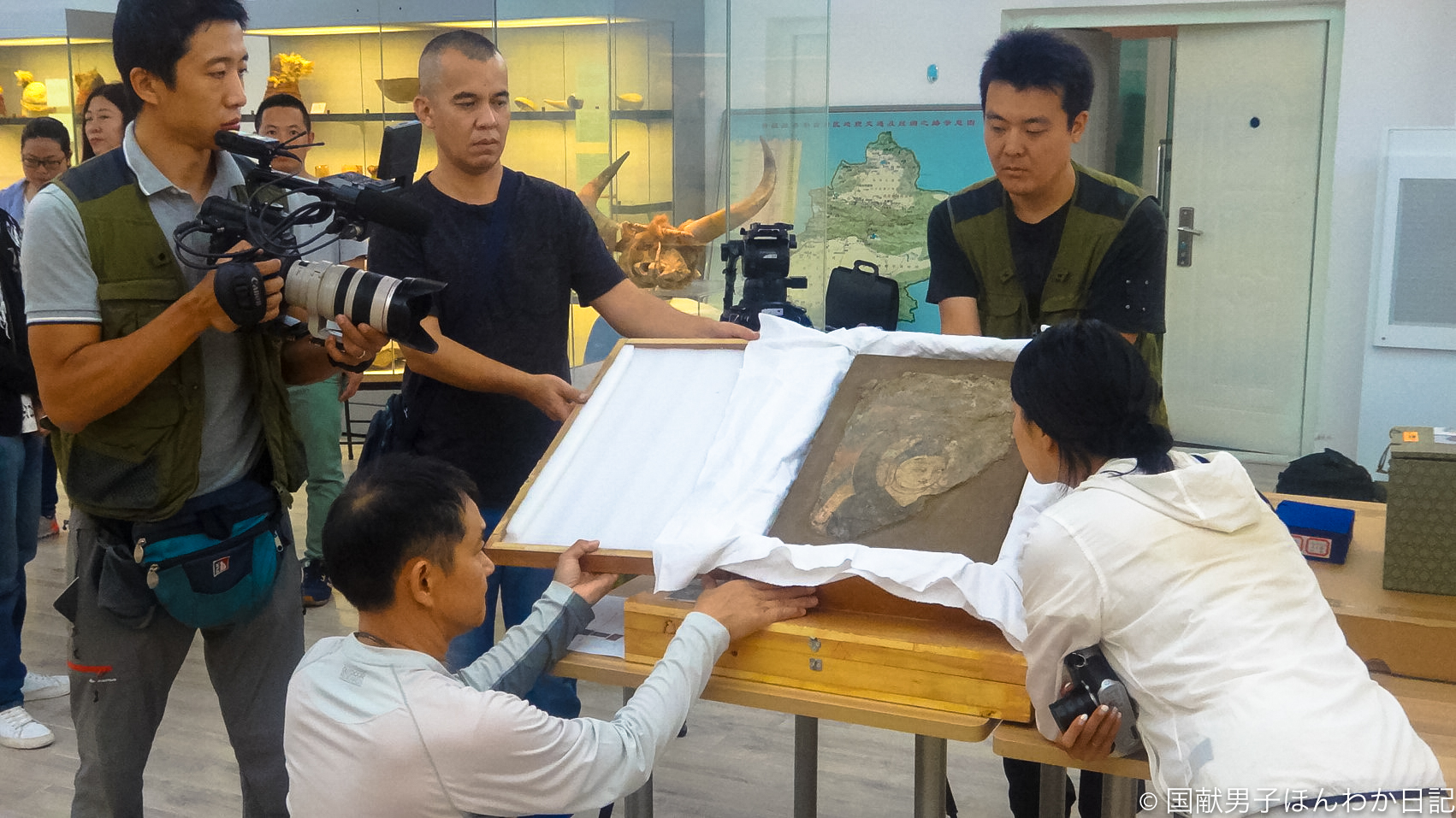 日中共同隊がダンダンウイリクで発掘した「西域のモナリザ」を撮影する一行(撮影:筆者)