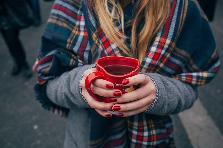 女生雙手捧著心型茶杯