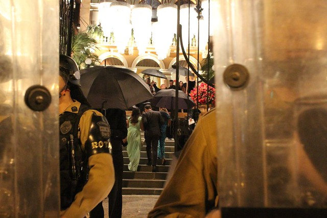 Convidados da festa usaram guarda-chuvas como escudo de proteção contra ovos arremessados pelos manifestantes - Créditos: Giorgia Prates