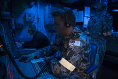 Royal Australian Navy Sailor Able Seaman Combat Systems Operator Samuel Perkins communicates with ships of the U.S.-Australia expeditionary strike group from the combat information center aboard the USS Bonhomme Richard (LHD 6) during Talisman Saber 17, July 7. (U.S. Navy/MC2 Cameron McCulloch)