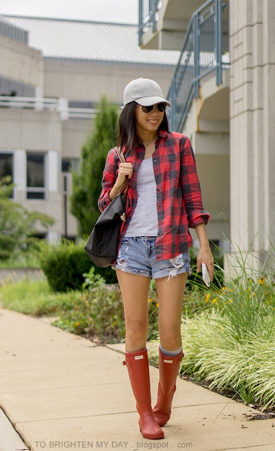 gray baseball cap, buffalo red check shirt, gray tank, distressed shorts, black tote, red rain boots