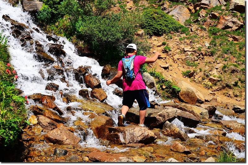 Jacob crossing a waterfall stream on the Arapaho Pass trail 1