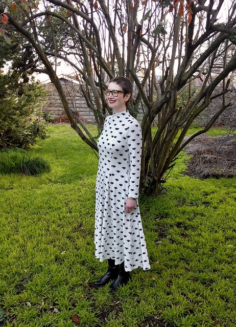 Woman stands in a garden. She wears a dramatic maxi dress in eye print.
