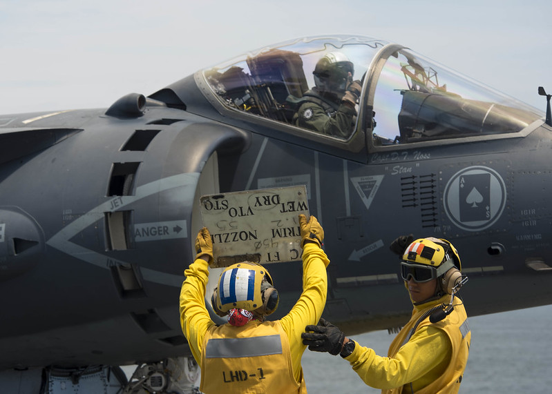 Sailor uses a tote board to communicate with the pilot of an AV-8B Harrier.A