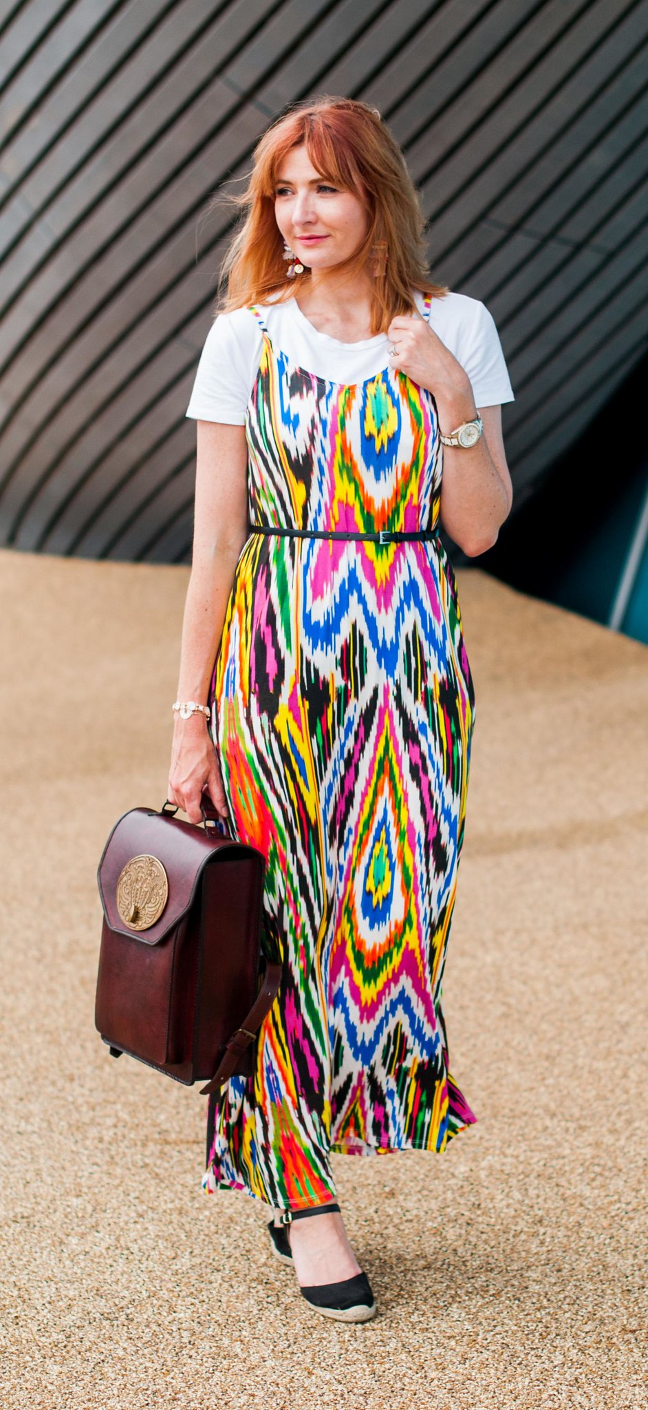 A rainbow-bright summer maxi dress styled in 90s style: Multi-coloured strappy maxi dress \ plain white t-shirt tee \ black wedge espadrilles \ Beara Beara brown leather backpack with antique brass plaque | Not Dressed As Lamb, over 40 style