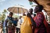 "Kahanbu Mastayabo, 26 (left) protects her six-months-old daughter, Esther, from the strong sun light with an umbrella at the e-voucher market in Kanyabayonga while her husband, Muhinto Meso, 23, (second from right) receives a bag of cassava roots.   The family was displaced by armed groups in November 2016. ""My grandfather was killed with a machete,"" Kahanbu Mastayabo says candidly.   © NRC/Christian Jepsen"