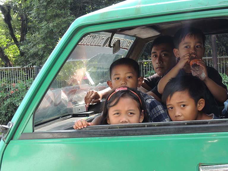 綠色車子裡的爸爸和四個小孩