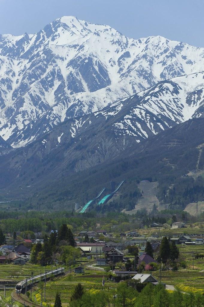残雪の五竜岳と特急あずさ