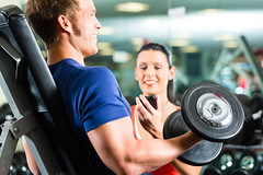 Man or Bodybuilder with his personal fitness trainer in the gym exercising sport with dumbbells, clo