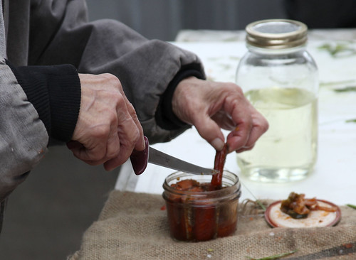 Mary Lou Bottorff pulls smoked salmon from a jar for participants to sample at the end of the workshop.