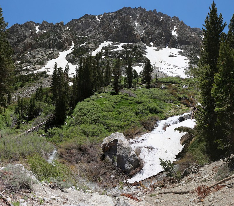 The North Fork of Bishop Creek flows under a snow bridge on the Paiute Pass Trail
