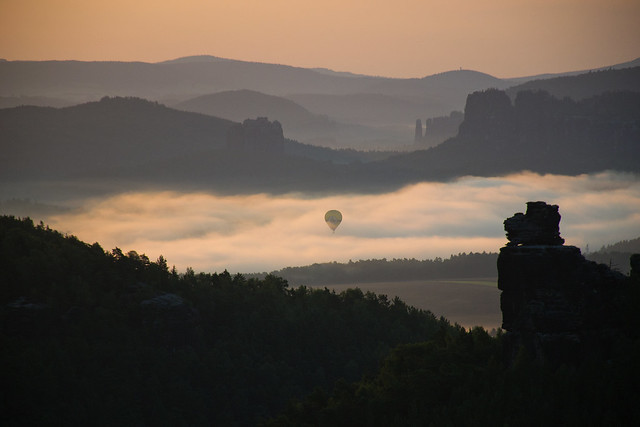Balloon rising out of the morning fog