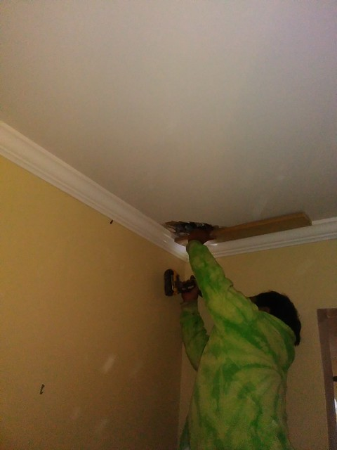 A man in a tie-tye sweatshirt uses a drill to cover a hole in the ceiling two two-by-fours.
